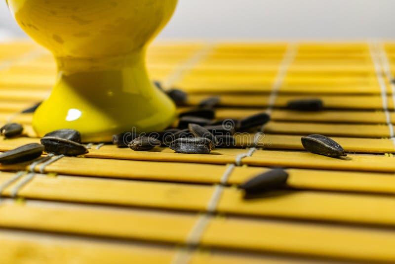 Черные небольшие семена подсолнуха Нажмите на семена с шелухами Пригорошня в желтой миниатюрной стойке на деревянной салфетке Раз стоковая фотография rf