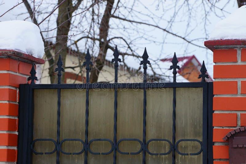 Черные острые стальные пруты на воротах металла и части кирпича обнесут забором белый снег стоковое изображение rf
