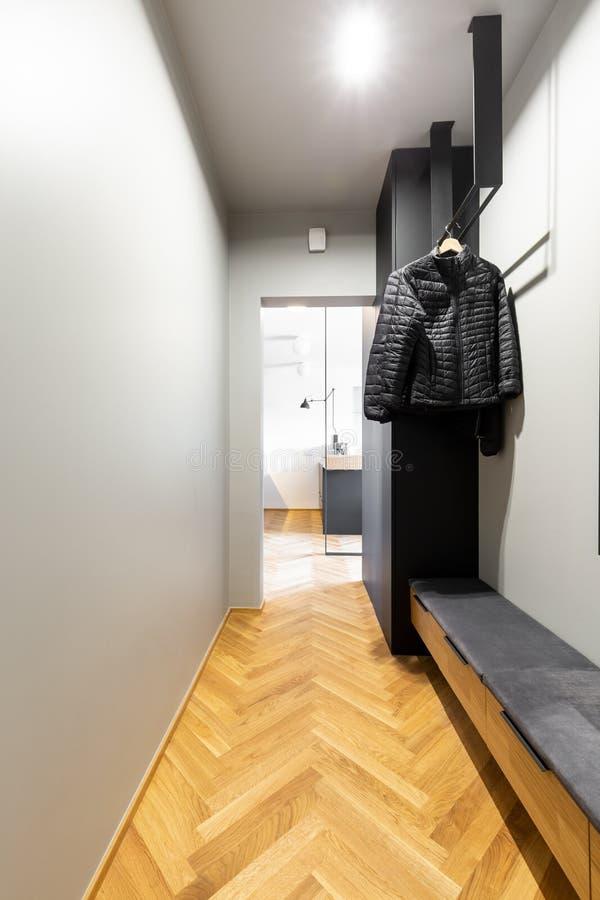 Черные пальто на творческой, промышленной вешалке в inte входа стоковое изображение