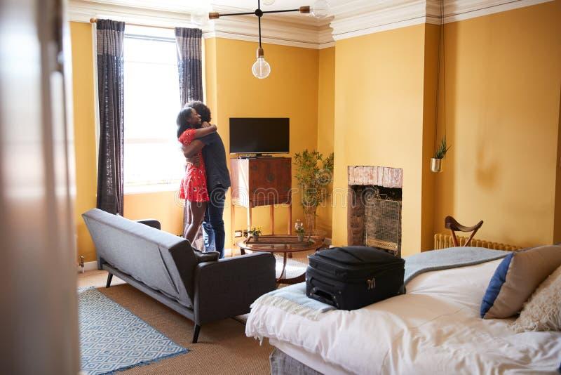 Черные пары обнимая в гостиничном номере, во всю длину стоковые фото