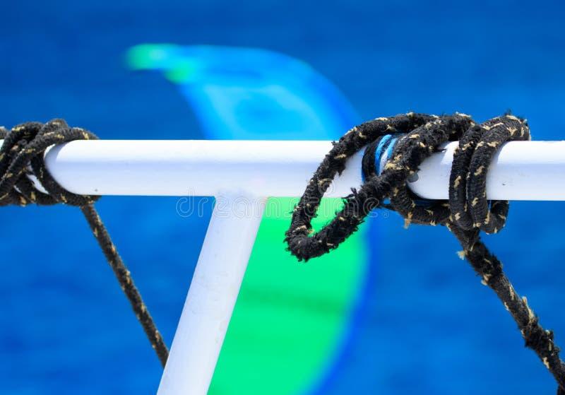 Черные плавая веревочки пересекая в узлы связи вокруг трубки шлюпки белой на запачканной темносиней предпосылке морской воды, жив стоковые фотографии rf