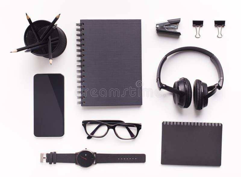 Черные предметы снабжения в официальном стиле, очки и наушники, мобильные телефоны стоковые фотографии rf