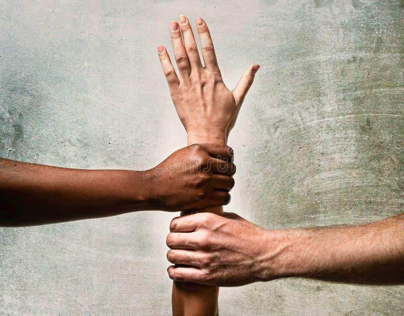 Черные руки афроамериканца и кавказца держа совместно белую руку кожи в единстве мира стоковая фотография