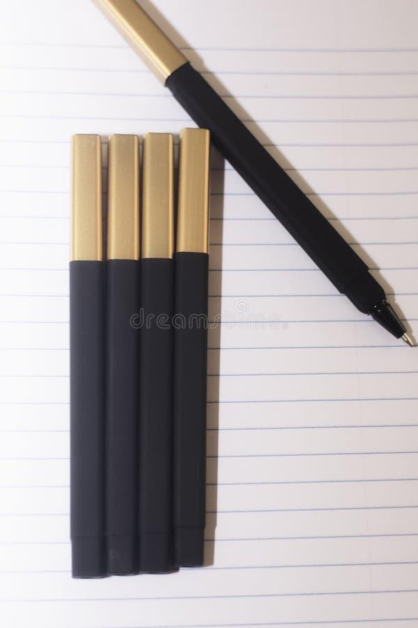 Черные ручки на выровнянном мире белой бумаги, подготавливают для того чтобы пойти назад к школе или быть канцелярские товаром стоковые изображения rf