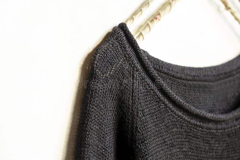 Черные свитер или отрезок шьют висеть на вешалке одежд на белизне конец вверх стоковое изображение