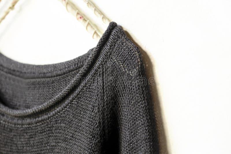Черные свитер или отрезок шьют висеть на вешалке одежд на белизне конец вверх стоковое изображение rf