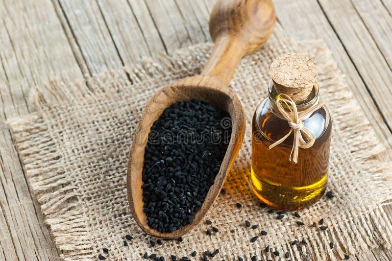 Черные семена и эфирное масло тимона с шаром и деревянными лопаткоулавливателем или ложкой стоковые изображения