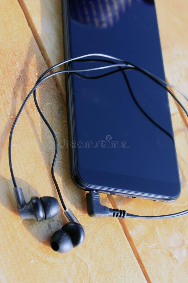 Черные смартфон и наушники на деревянной русой предпосылке стоковые изображения rf