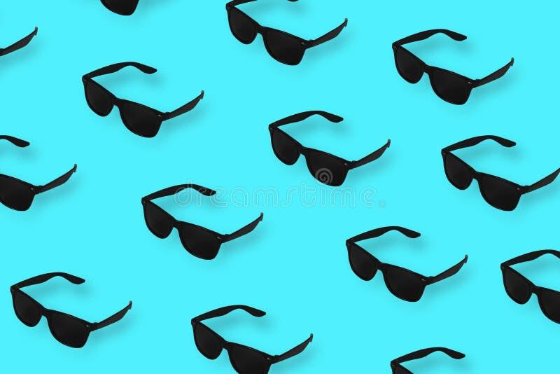 Черные солнечные очки картины на пастельной голубой предпосылке E стоковые фото