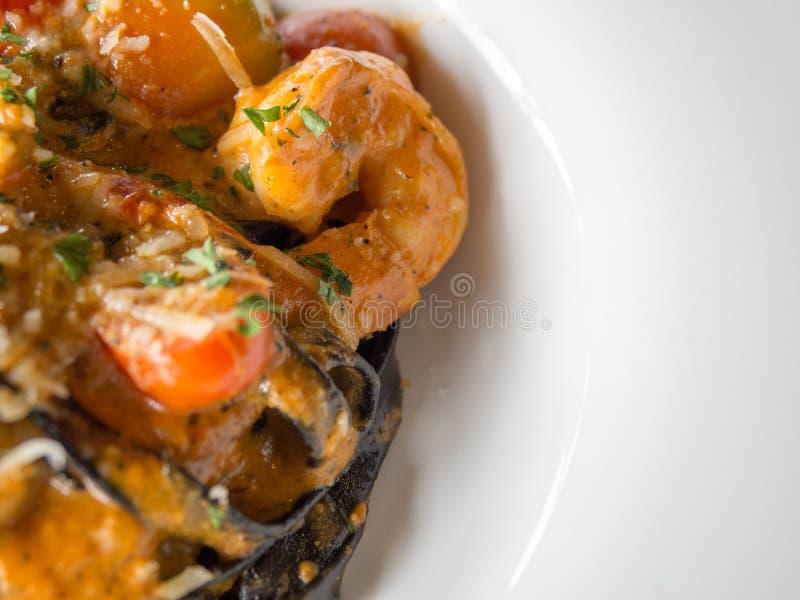 Черные спагетти в томатном соусе с креветкой, томатом брызгают с специями и сыром на белой плите Свежий и чистый взгляд блюд стоковое изображение