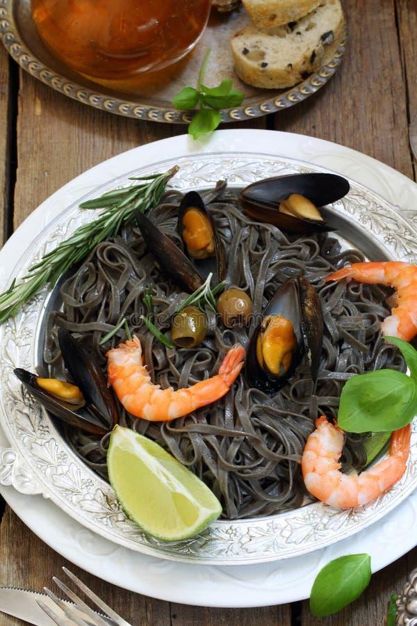 Черные спагетти с мидиями, креветкой и томатами стоковые изображения