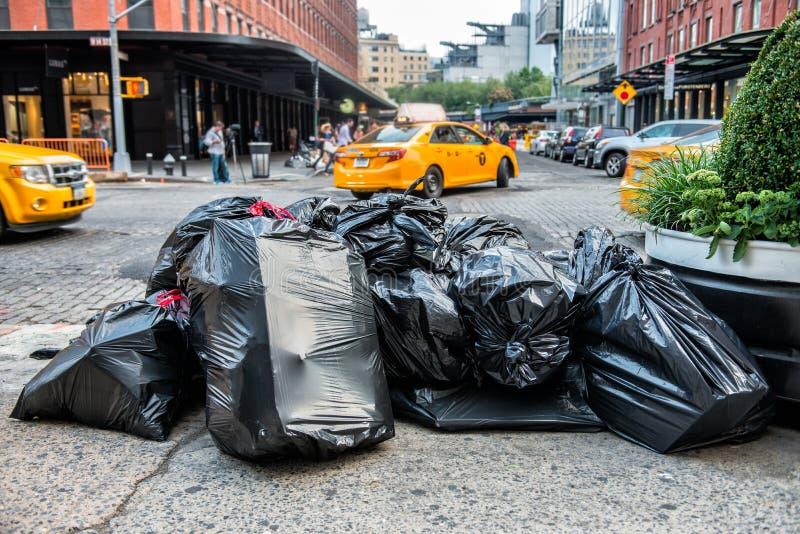 Черные сумки погани на тротуаре в тележке погани обслуживания улицы Нью-Йорка ждать Отброс упакованный в больших мешках для мусор стоковые фото