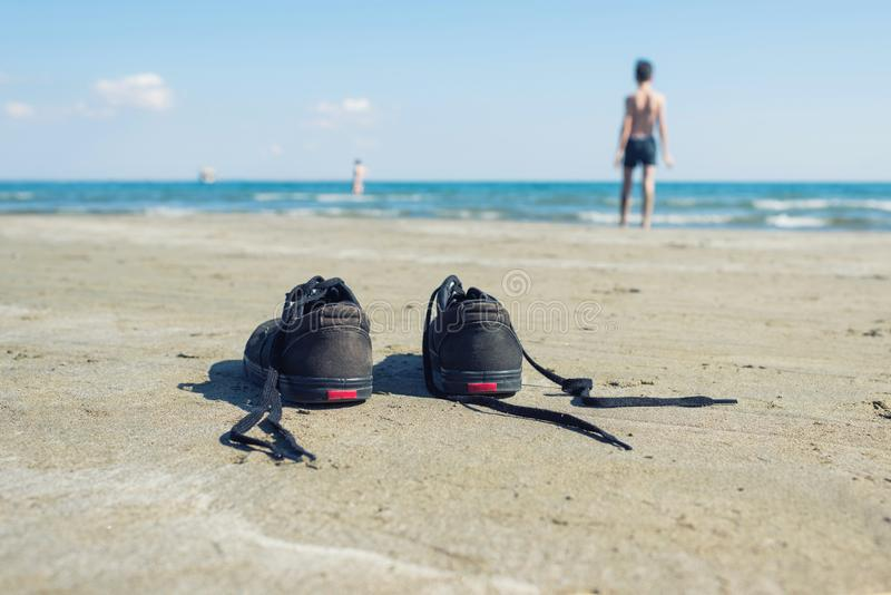 Черные тапки на песке на предпосылке моря и мальчика Лето и концепция перемещения стоковое изображение rf