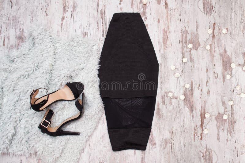 Черные юбка и ботинки на деревянной предпосылке Модное concep стоковые фотографии rf