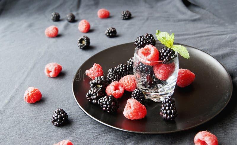 Черные ягоды и поленики в стеклянной чашке стоковое фото rf
