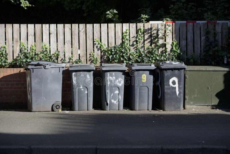 Черные ящики wheelie в ряд на улице с номерами дома напечатали на передних ждать людях ящика для того чтобы собрать стоковое фото rf