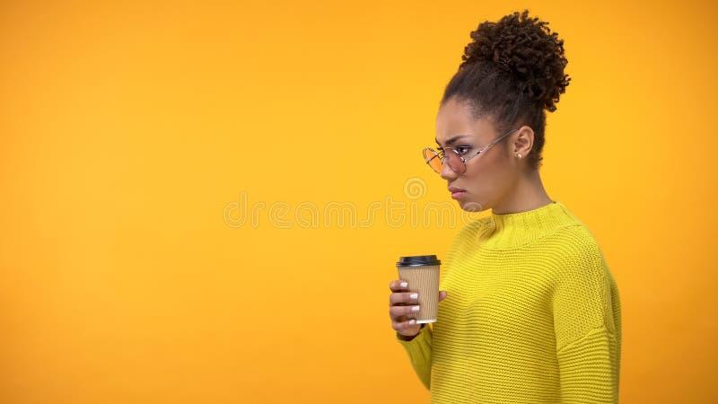 Черные eyeglasses девушки держа опостылеть кофейную чашку, вкус -вкуса, обс стоковые изображения rf