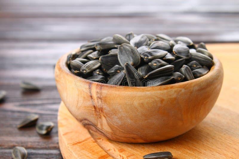 Черные unrefined семена подсолнуха в деревянном шаре на деревянном столе стоковые фото