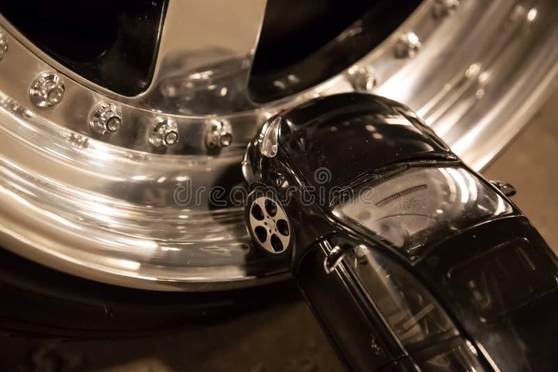 Черный автомобиль игрушки остается на оправах сплава реального автомобиля Изготовленные на заказ настраивая колеса стоковые изображения