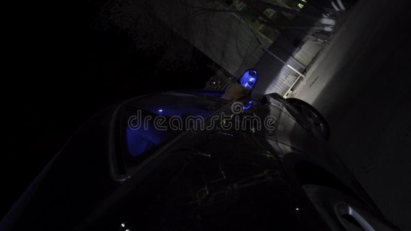 Черный автомобиль moder двигая в улицы города вечером со светами СИД автомобиля shimmer в других цветах footage Автомобиль стоковые изображения rf