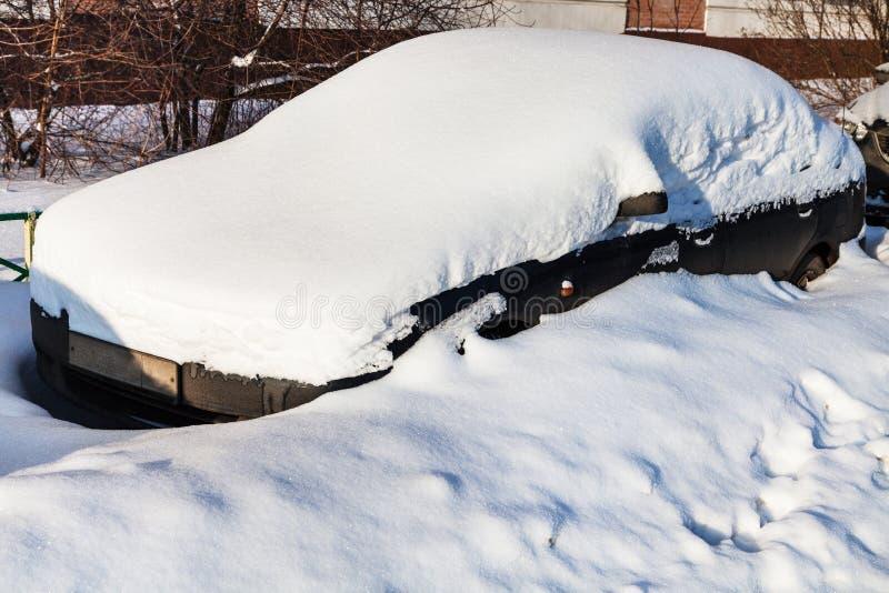 Черный автомобиль под свежим снегом в месте для стоянки стоковые изображения rf