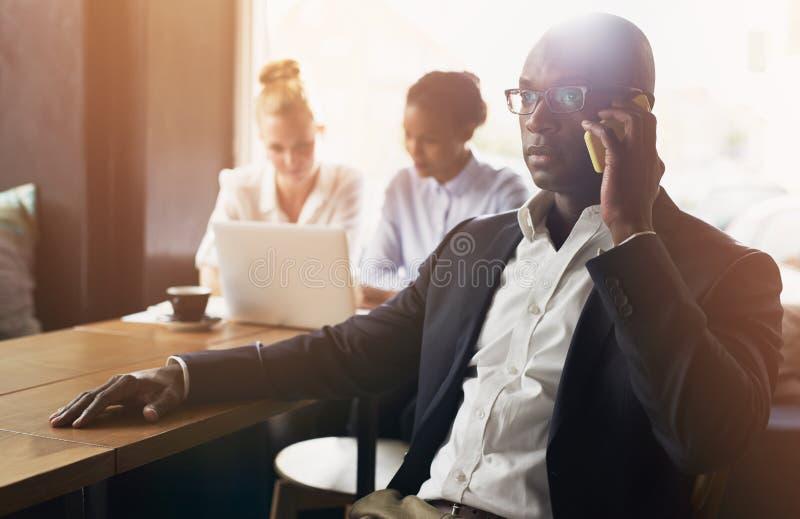 Черный бизнесмен используя сотовый телефон стоковое фото