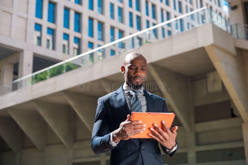 Черный бизнесмен смотря его планшет в городском backgr стоковые изображения