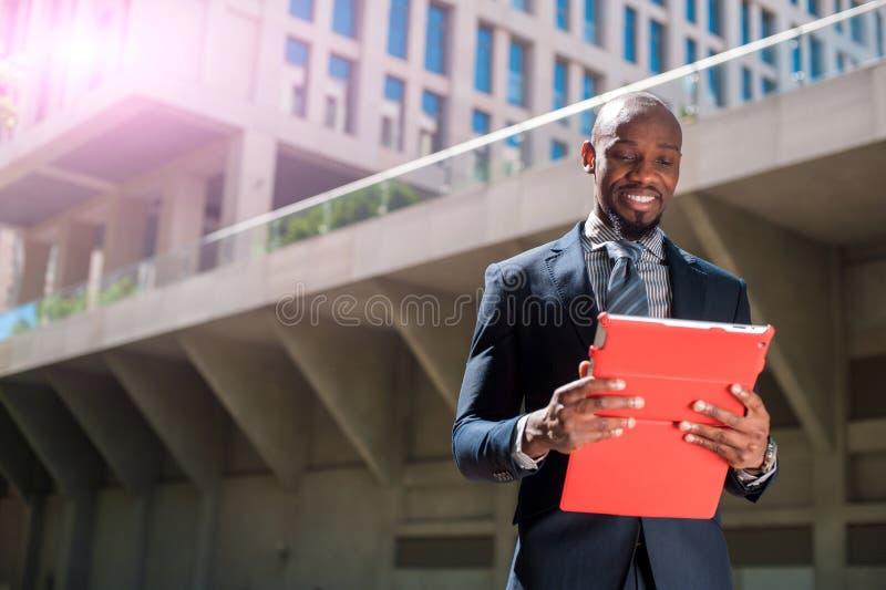 Черный бизнесмен смотря его планшет в городском backgr стоковая фотография rf