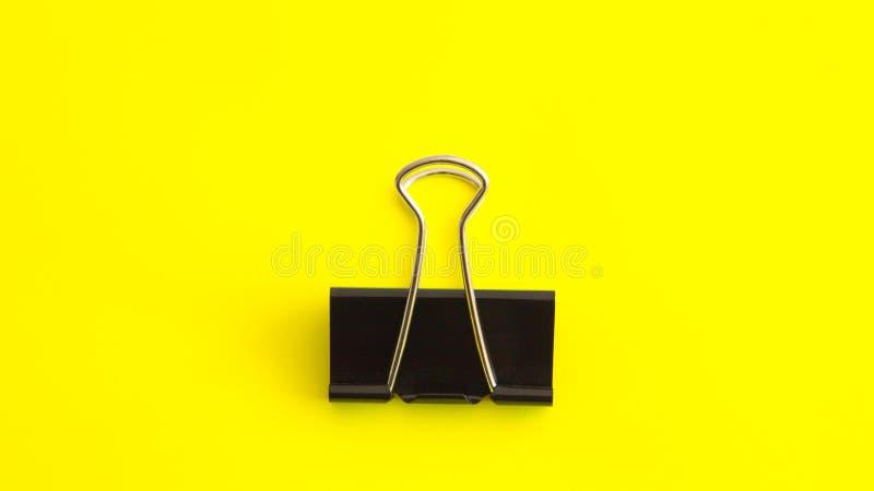 Черный бумажный зажим на желтой предпосылке - изображении стоковое изображение rf