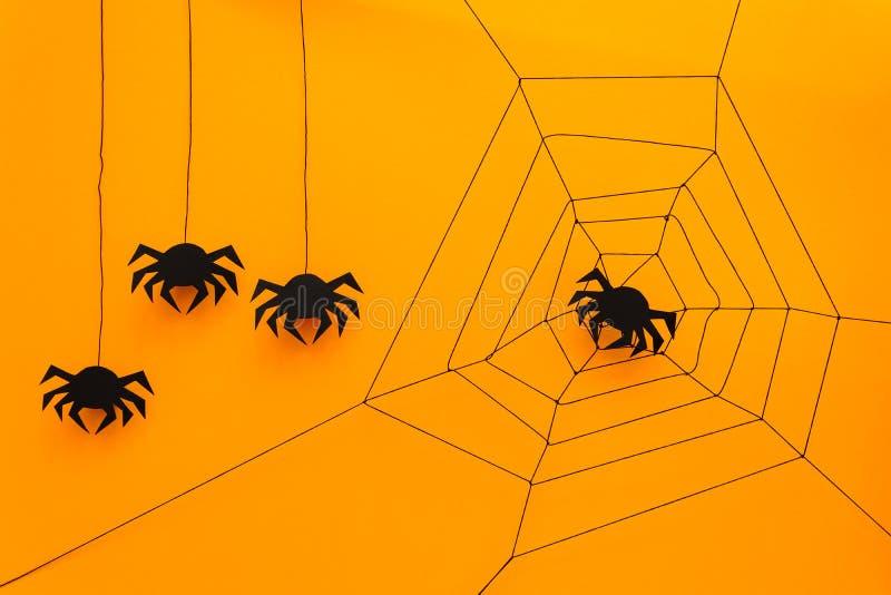 Черный бумажный паук с сетью на желтой предпосылке удерживания halloween даты принципиальной схемы календара жнец мрачного счастл стоковая фотография