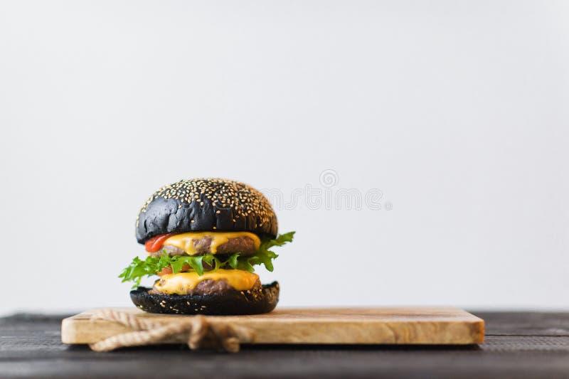 Черный бургер на деревянной прерывая доске, серой предпосылке стоковое изображение rf