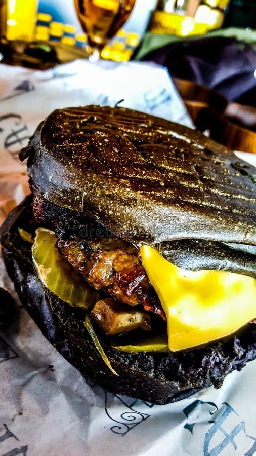 Черный бургер с сыром, грибами и соленьем чеддера стоковые фото