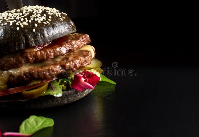 Черный двойной гамбургер сделанный от говядины, с перцем jalapeno Большой конец вверх стоковые фотографии rf