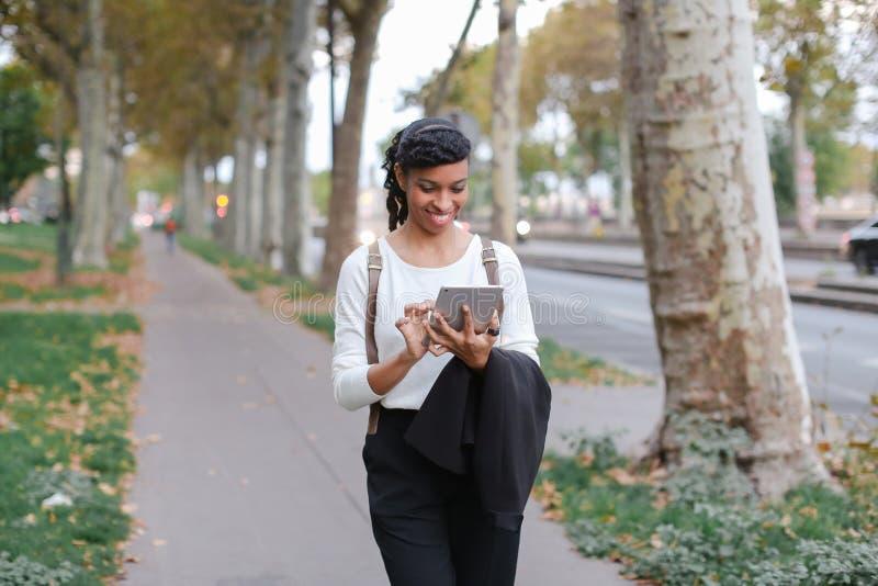 Черный женский красивый студент используя таблетку и идущ на улицу с деревьями стоковое фото