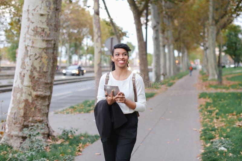 Черный женский милый студент используя таблетку и идущ на улицу с деревьями стоковое фото