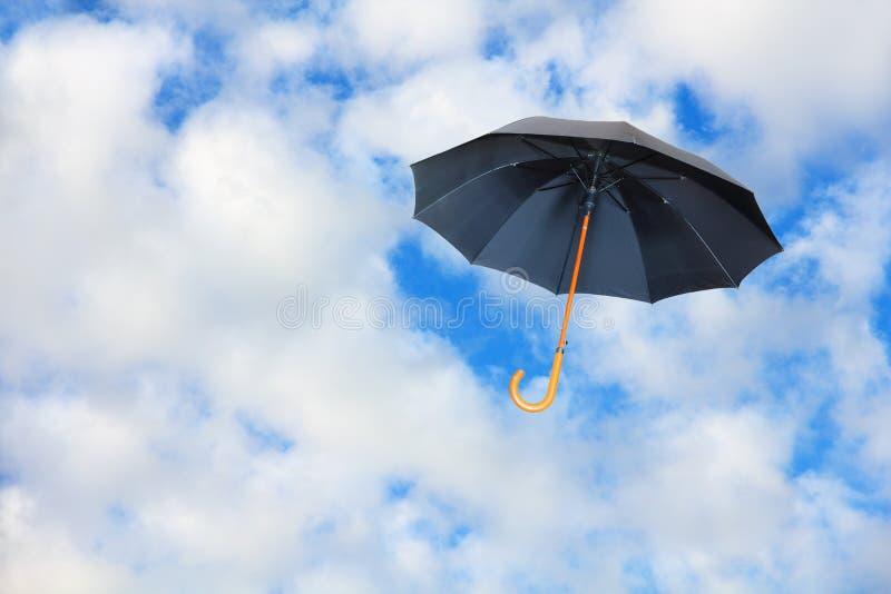 Черный зонтик летает в небо против чисто белых облаков Ветер  стоковые фотографии rf