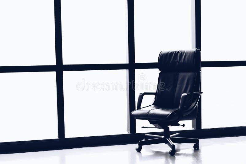 Черный исполнительный кожаный стул в пустых размерах офиса с большим окном стоковое фото