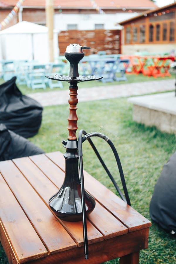 Черный кальян на деревянном столе снаружи Концепция образа жизни предпосылки Кальян на открытом воздухе в лете стоковые изображения