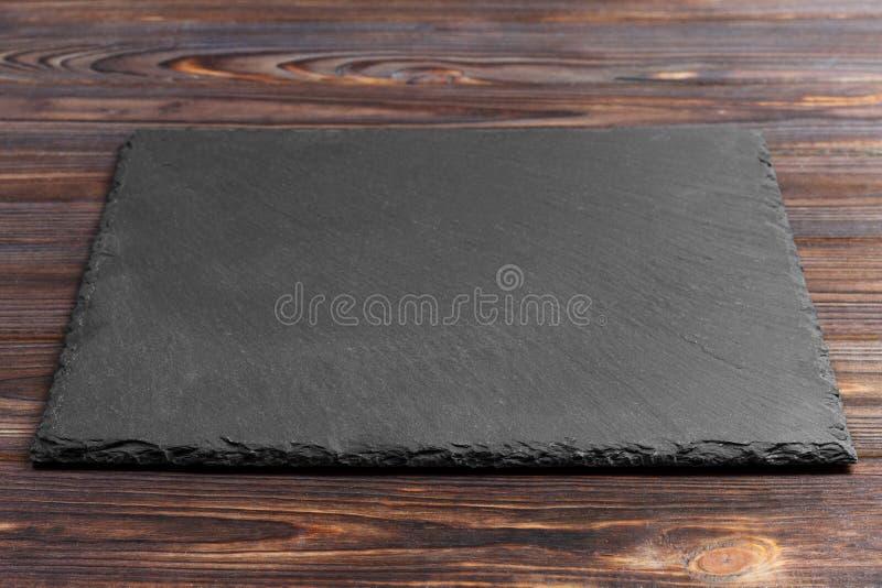 Черный камень шифера на деревянной предпосылке скопируйте космос стоковая фотография