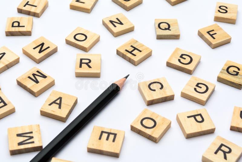 Черный карандаш и разбросанные письма алфавита на деревянных блоках на белой предпосылке стоковые изображения