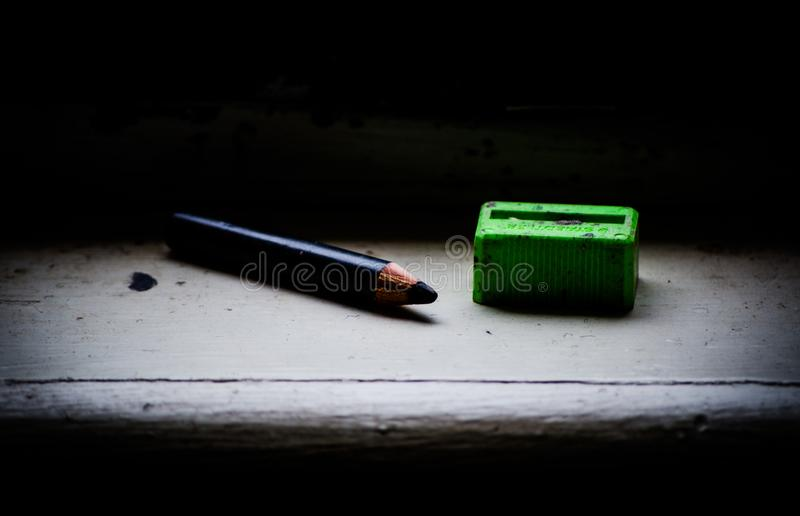 Черный карандаш цвета с старой зеленой точилкой для карандашей, изображением в темном свете тона стоковые фото