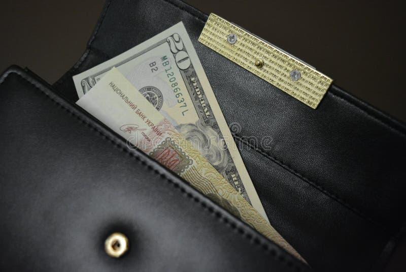 Черный кожаный бумажник с деньгами в ей на коричневой штейновой предпосылке Банкноты 20 20 американских долларов и 100 100 Ukrain стоковые фотографии rf