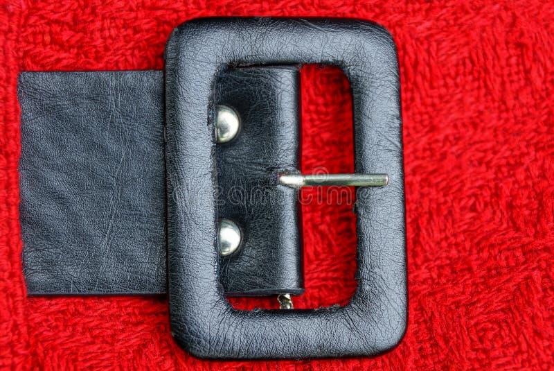 Черный кожаный пояс с большой пряжкой на красной ткани шерстей стоковые фото