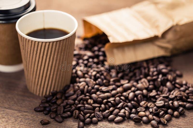 Черный кофе в бумажном стаканчике и фасолях стоковые изображения