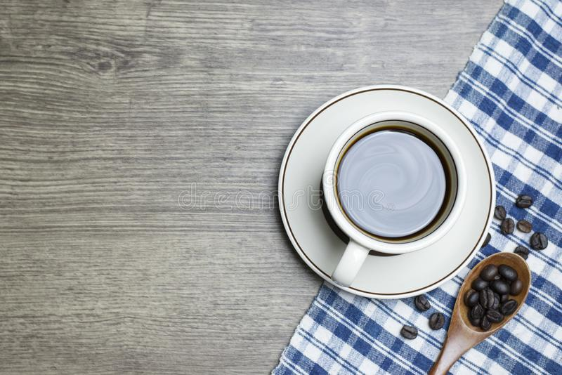 Черный кофе интенсивный в чашке и деревянным кофейных зернах ложки зажаренных в духовке ветроуловителем стоковые фотографии rf