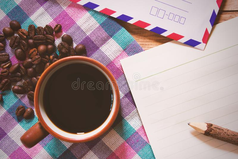 Черный кофе и Notepaper и карандаш на деревянном столе стоковое фото