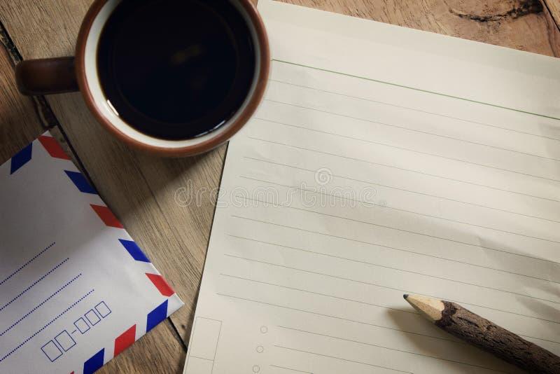 Черный кофе и Notepaper и карандаш на деревянном столе стоковые изображения rf