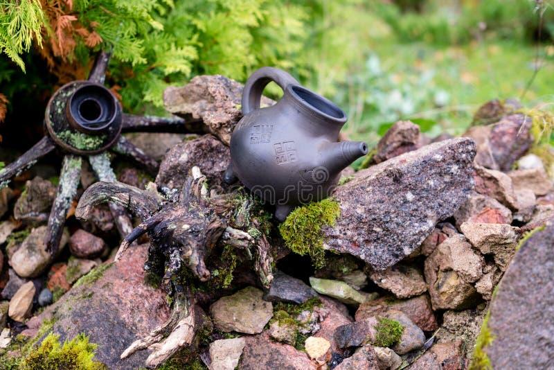 Черный кувшин глины и старый деревянный бочонок на каменной куче стоковая фотография