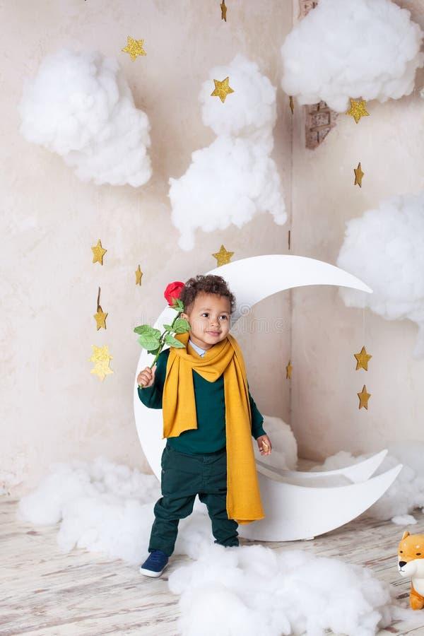 Черный мальчик в зеленом свитере и желтом усмехаться шарфа День женщин! Немногое черный мальчик с розой Поздравления на празднике стоковое изображение