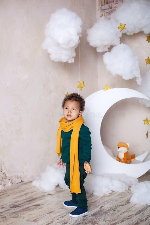 Черный мальчик стоит около месяца, nluna, среди звезд Ребенок в игре, в фантазии Приключения маленького принца Afric стоковые фотографии rf